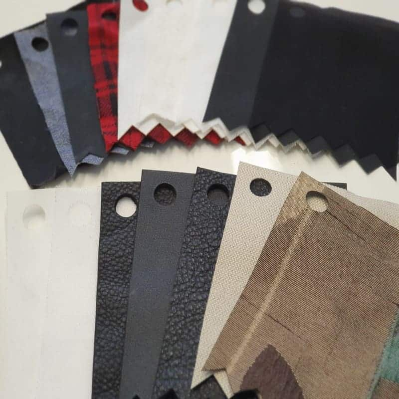 Laser cut Fabrics & Leather swatches of various colours arrayed in a fan