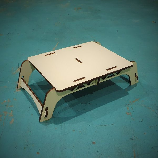 side view of Monitor Stand made from Plywood on a green concrete floor